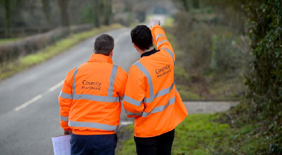 county broadband engineers wearing orange jackets point at a road